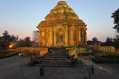 "Night view of the Konark Temple. The main Temple was called by European sailers ""The Black Pagoda"" as it formed an important landmark for them in their coastal voyage. Contrasting to this , the white washed Temple of Lord Jagannath at Puri was known as the white pagoda.   Konark Sun Temple in Orissa belongs to the Kalinga school of Indian temples and was constructed by King Narasimhadeva of the Eastern Ganga Dynasty in the 13th Century. This world heritage site temple takes the form of a colossal chariot of Surya (Sun) drawn by seven spirited horses on twelve pairs of exquitely decorated wheels. Surya has been a popular deity in India since the Vedic perios. Thousands of sculptured images depict deities, celestial and human musicians, dancers, lovers, and myriad scenes of courtly life, ranging from hunts and military battles to the pleasures of courtly relaxation. The temple is famous for its erotic stone sculptures, which can be found primarily on the second level of the porch structure."