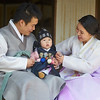 A young family in traditional Korean garb during a photo shoot at Unhyun Palace (운현궁), former residence of Prince Regent Daewon-gun, ruler of Korea during the Joseon Dynasty in the 19th century, and father of Emperor Gojong.