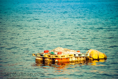An old fishing raft floating in a harbor