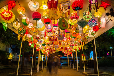 Festive illuminated lanterns hanging over a walking path