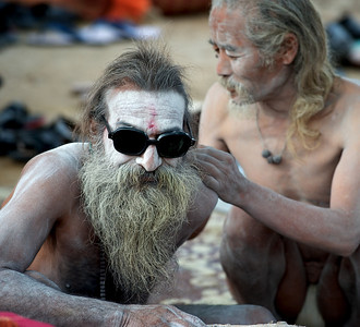 Cool Naga Baba getting his back covered with ashes. Kumbh Mela 2010, Haridwar.