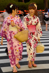 "Japanese lady dressed in the kimono (着物?). Kimono is a Japanese traditional garment. The word ""kimono"", which literally means a ""thing to wear"" (ki ""wear"" and mono ""thing""), has come to denote these full-length robes. Kimono are T-shaped, straight-lined robes worn so that the hem falls to the ankle, with attached collars and long, wide sleeves. Kimono are wrapped around the body, always with the left side over the right (except when dressing the dead for burial.), and secured by a sash called an obi, which is tied at the back. Kimono are generally worn with traditional footwear (especially zōri or geta) and split-toe socks (tabi)."