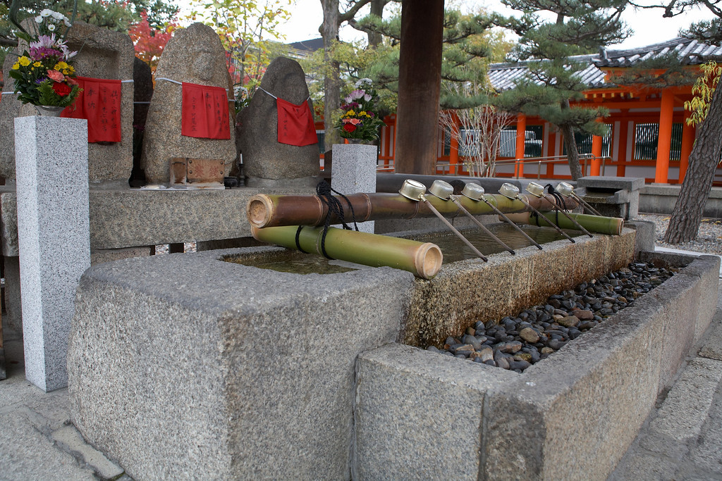 Visitors purify themselves by pouring water over their hands from this basin. The red clothing on the statues is an offering to unborn babies.