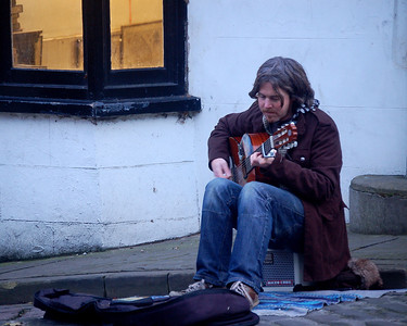 Street musician playing some sweet classical guitar to entertain the market goers on their long climb up Steep Hill