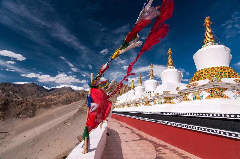 Prayer flags and Chortens overlook the Ladakh Range at Thiksey Gompa