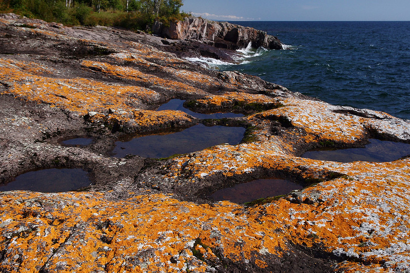 Orange lichens and water pockets on the rocky cliffs above Lake Superior. Temperance River State Park, Minnesota.
