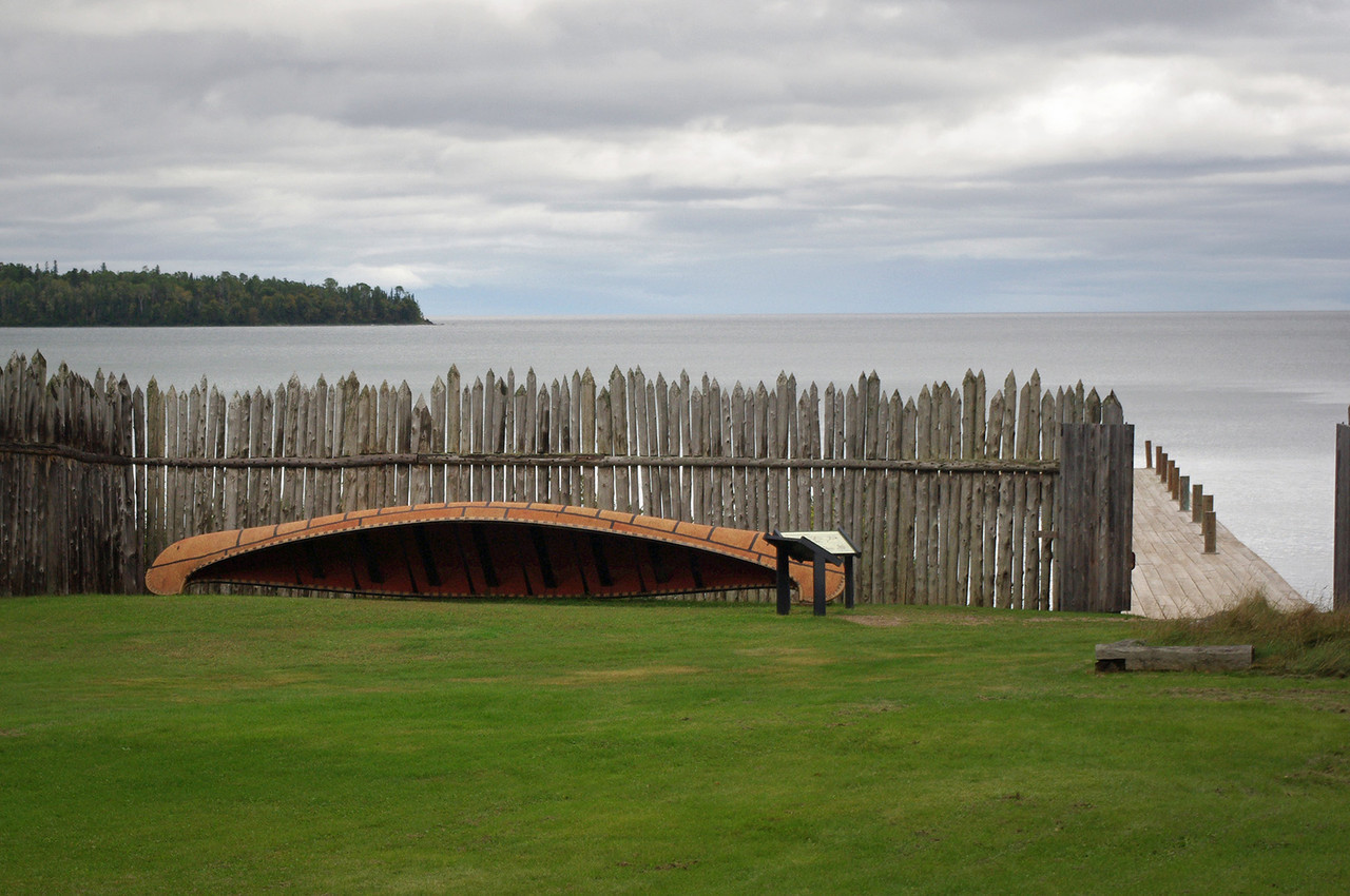 The Northwest Trading Company outpost is located near the Canadian border in Grand Portage National Monument. This view shows a replica voyager's canoe leaning against the palisade pole walls, with a view of Lake Superior.