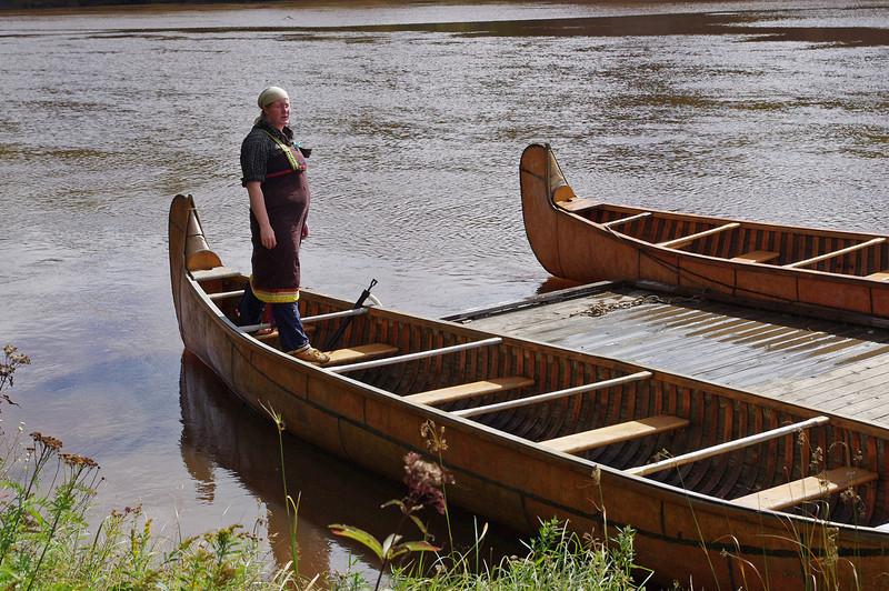 Guide standing in a big birchbark canoe, Fort William Historical Park, Ontario.