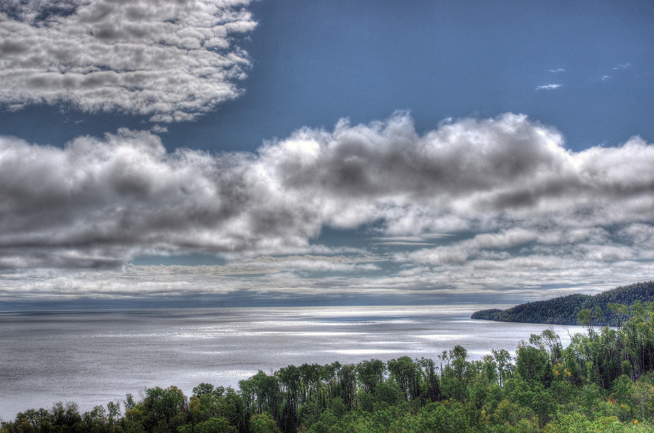 After two days of fog and one day of heavy rain, the sun breaks through the clouds over the North Shore of Minnesota's Lake Superior.