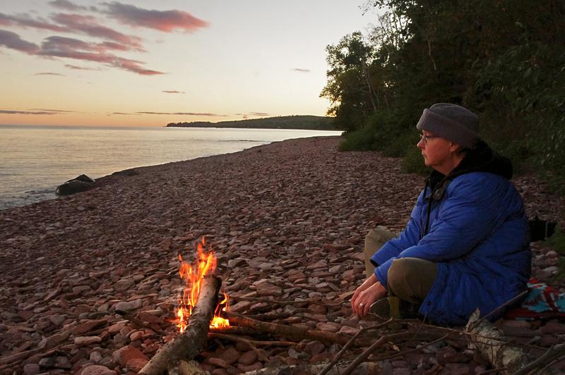 Rita beside a fire on Kadunce beach, Lake Superior, Minnesota, waiting for the moon to come up.
