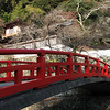 A traditional red bridge leading to a temple