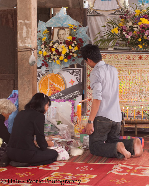 Grandson Makes An Offering In Front of His Grandfather's Coffin At the Family Home