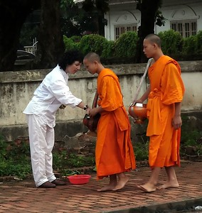 Of the 10,000 people of Luang, about 1500 are Buddhist monks, residing in a dozen temples. Every morning at  6, after several single drumbeats,  they walk through the town with their bowl collecting offerings of food.