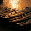 Long narrow boats, typical Mekong river craft, lay tied up on the bank at sunset.