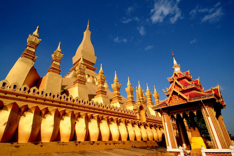 Wat Pha That Luang, with sacred lingam in pavilion at right.