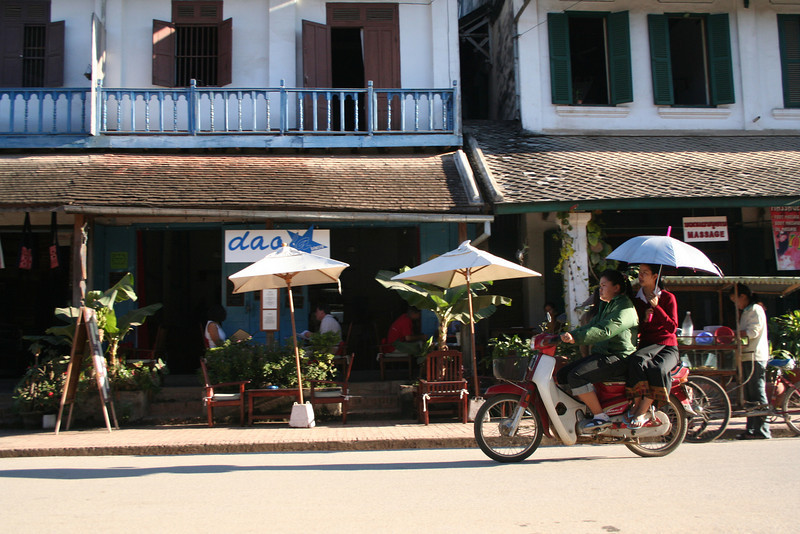 Three umbrellas, all in a row. Street scene in Luang Prabang.