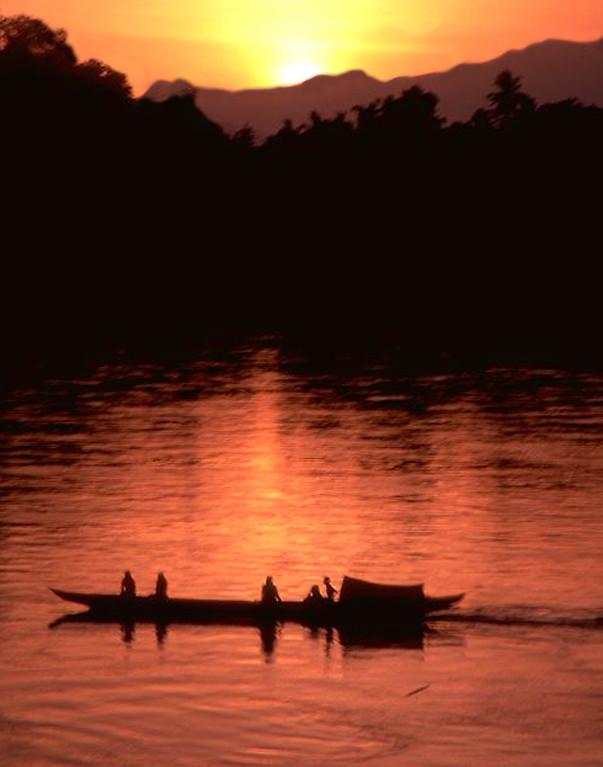 Mekong river sunset and long tail boat in Luang Prabang, Laos