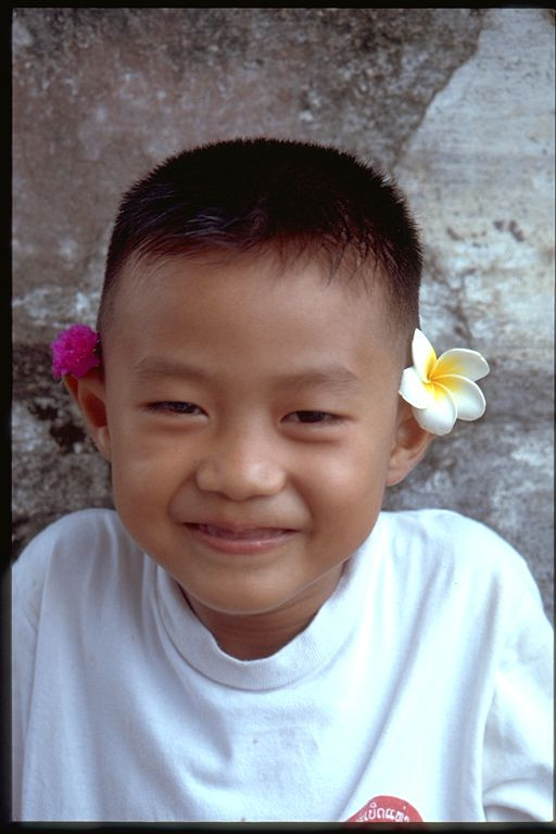 Boy with flowers and a smile, Laos