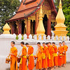 Novice Buddhist monks line up outside their Wat to receive alms. <br /> <br /> Because entering the monkhood is major merit-generating act, most men spend part of their lives as monks. A young man will be initiated at about 5 years of age as a novice monk and remain in the monkhood temporarily, for several days to several months. His initiation, a ritual reenactment of the Buddha's own renunciation of material wealth and assumption of monastic discipline, is a major festive occasion. The initiate's head is shaved, he receives a new name, recites the monastic vows, and dons the monk's robe.<br /> <br /> During his monkhood the novice obeys the same rules governing diet, celibacy, and material possessions that discipline the senior monks. He lives in the temple monastery, collect his morning food in the community and recites the sacred texts. Temporary monks may return later in life either for another short period or to enter the monkhood permanently.