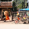 Luang Prabang street scene with monks, umbrellas and tuk-tuk.