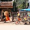 Luang Prabang street scene with monks, umbrellas and tuk-tuk.