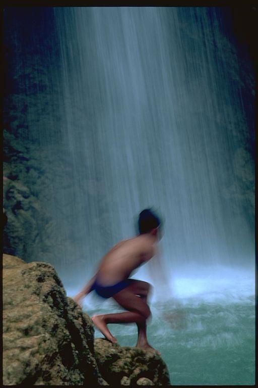 Boy under waterfall in Laung Prabang, Laos
