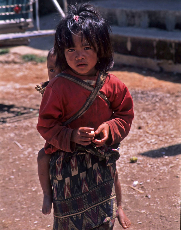 Small girl with baby on back in Laos