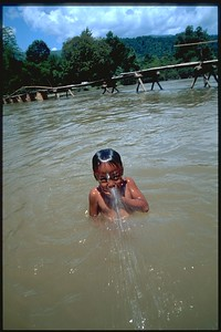 Boy playing in Mekong River Vang Viene, Laos