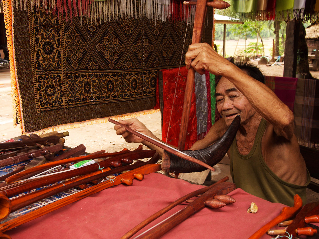 a sweet old man playing a sweet lao instrument
