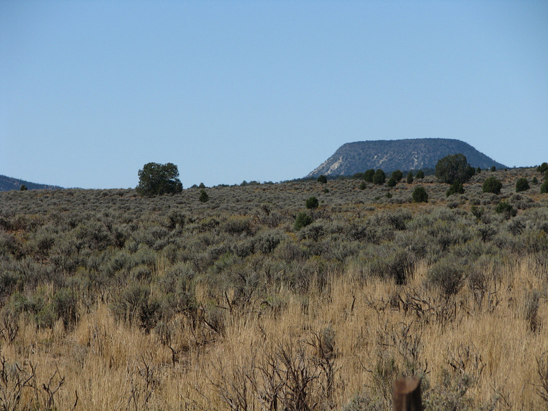 In the distance a cinder cone sleeps with its blanket of green covering it.
