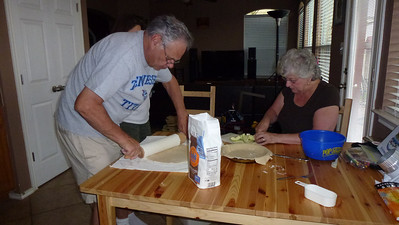 Dad and Mom making an apple pie.