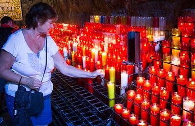 Judi lights a candle.