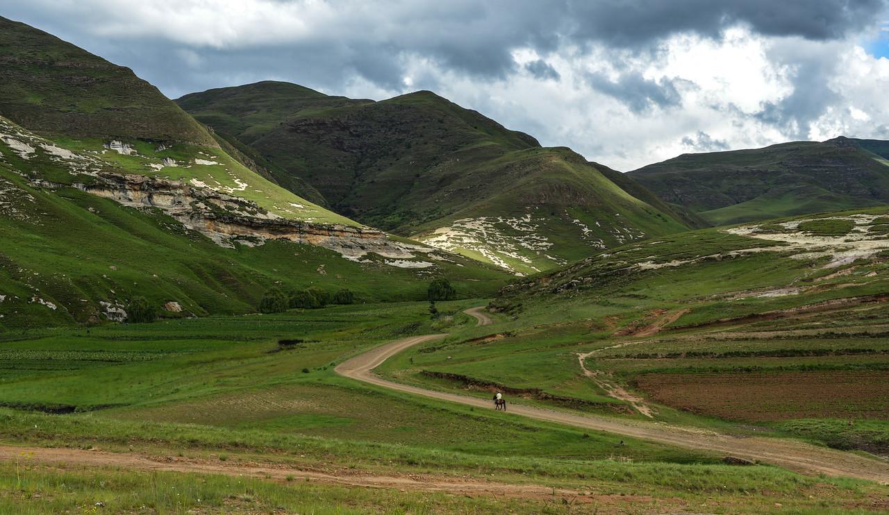 Mounted Sotho Man riding away into Lesotho Landscape