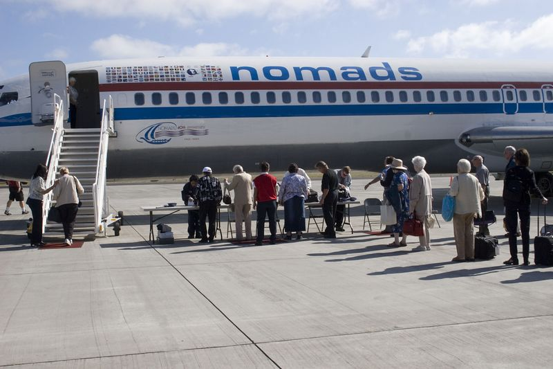Air transportation, airplane: Boeing 727 jet passenger plane, Clubhouse of the Nomads Travel Club, being boarded by Nomad Members at the end of the Lewis and Clark Trail trip on the Columbia, Snake, and Clearwater rivers, from the Bitterroot Mountains to the Pacific Ocean. The plane is housed at its air terminal at Detroit Metro Airport in Michigan. Portland International Airport, Oregon, July 2005.