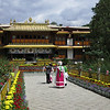 "Chinese tourists get a photo with ""traditionally dressed"" Tibetan girls at the Norbulingka Summer Palace of the Dalai Lamas."