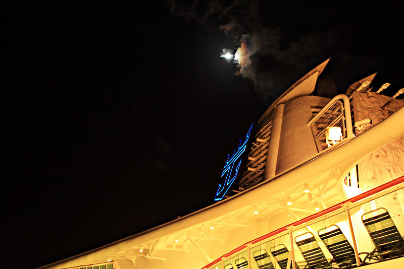 The full moon just about to peek out from the clouds above the Serenade of the Seas