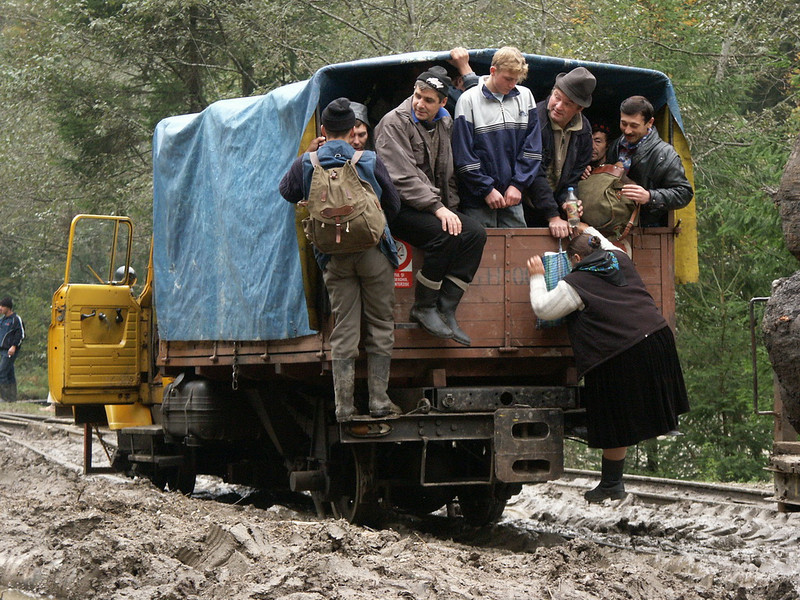 """None of this men helps the woman struggling to get in the rail-lorry ! Viseul de Sus, Valeea Vaserului, Maramures, Romania, 2004<br /> Beside steam engines, some strange cars, vans or even this """"Bucegi"""" V8 gasoline engined lorry are to be seen on Valea Vaserului railroad.<br /> This is the last narrow gauge steam traction railway in Europe"""