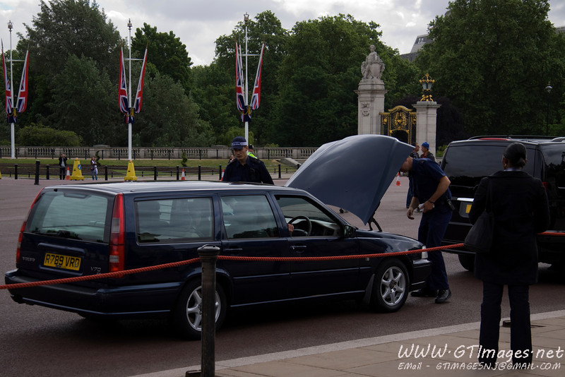 On this day, Prince Charles was giving awards of honor to citizens, and they were lined up at the gate to get in. All cars underwent a thorough inspection prior to being permitted entry. Here the guards are searching under the hood of this car.