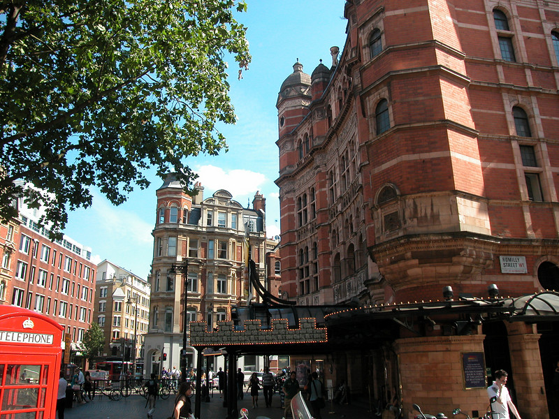 Soho. The towering Palace Theatre dominates Cambridge Circus. Five storeys of dark-red brick with octagonal towers on the top give it a looming aspect better suited to a court than a theatre. This sinister atmosphere is continued inside, with heavy blocks of marble, and Renaissance style arches in the foyer and stairwells.