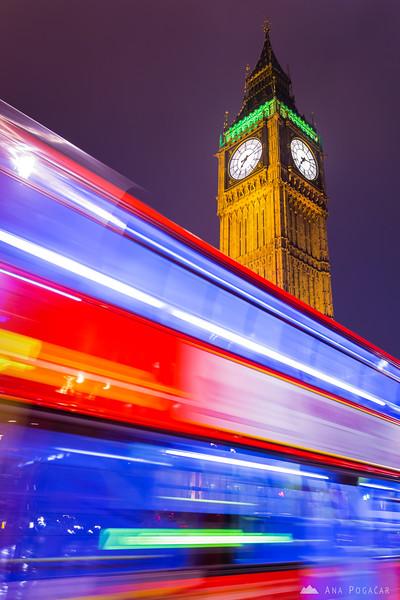 Red London doubledecker bus swishing past Big Ben at night.