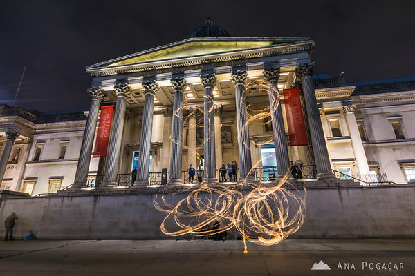 Torch juggler in front of the National Gallery at night