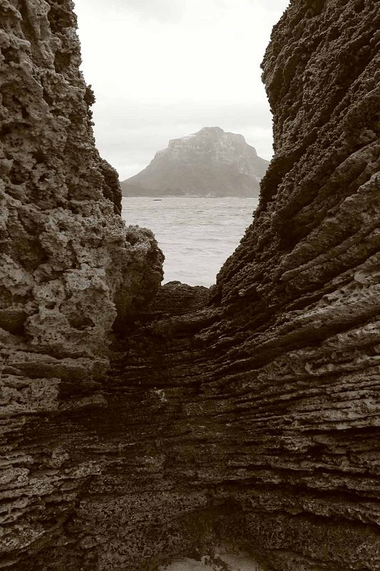 Mt.Lidgebird lies in the sea-spray view between the cleft in the rocks near Lover's Beach Lord Howe Island. In-camera sepia tones.