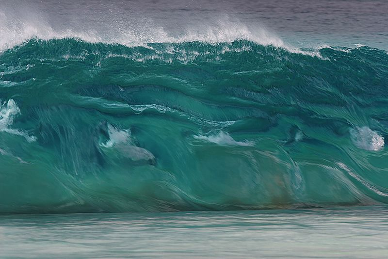 A green wave at Blinky's Beach. Shot with Canon 300mm L Image-Stabilised Lens. 1/125th@f6.3, 100ISO. While the wave looks huge, it was maybe 1 metre in height. Strong westerly wind blew the spume from the top of the wave.