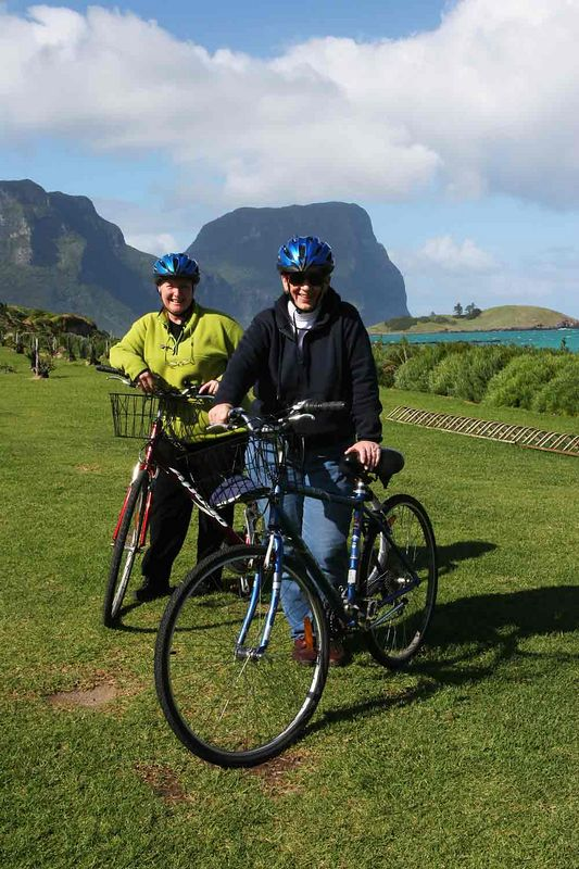 Gaye (in blue jacket) and Anne pose on their bikes with Mts.Lidgebird and Gower in the background . On the grass near the old flying-boat terminal at Lord Howe Island.