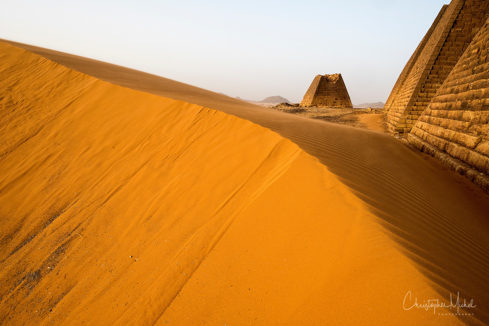 Wind sculpted san dunes surround the pyramids.