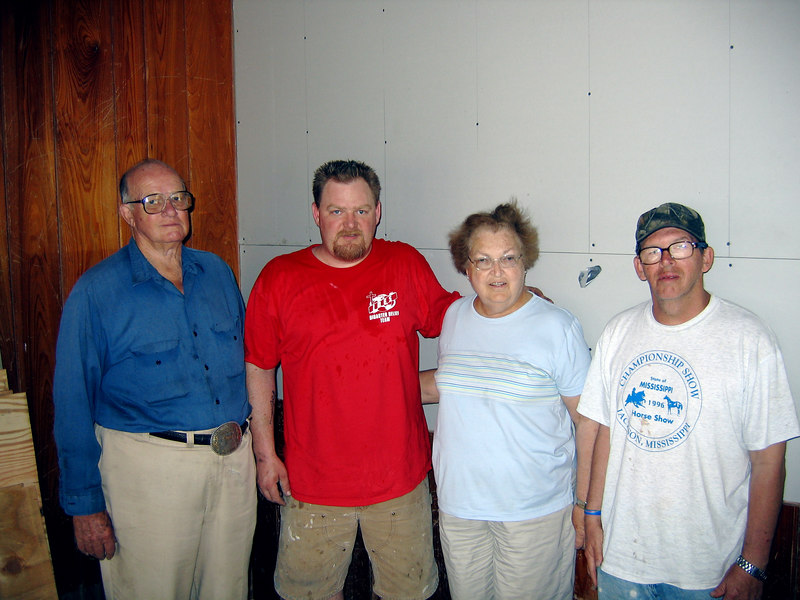 Steve standing with the Russ family. We hung drywall, insulated & installed French doors and two windows in their house.