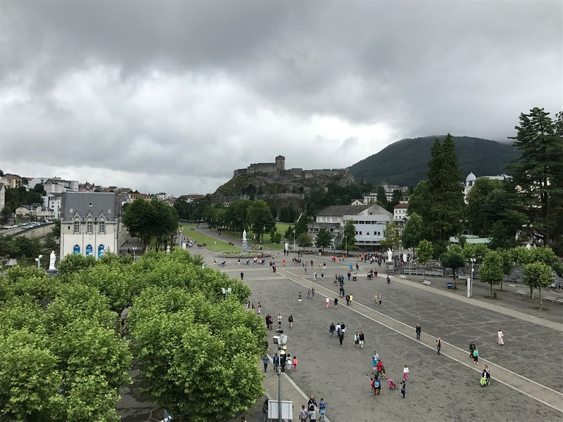 view from the ramp leading towards the upper sanctuary looking towards the entrance of the basilica grounds. The old fort can be seen in the center of the photo high above Lourdes