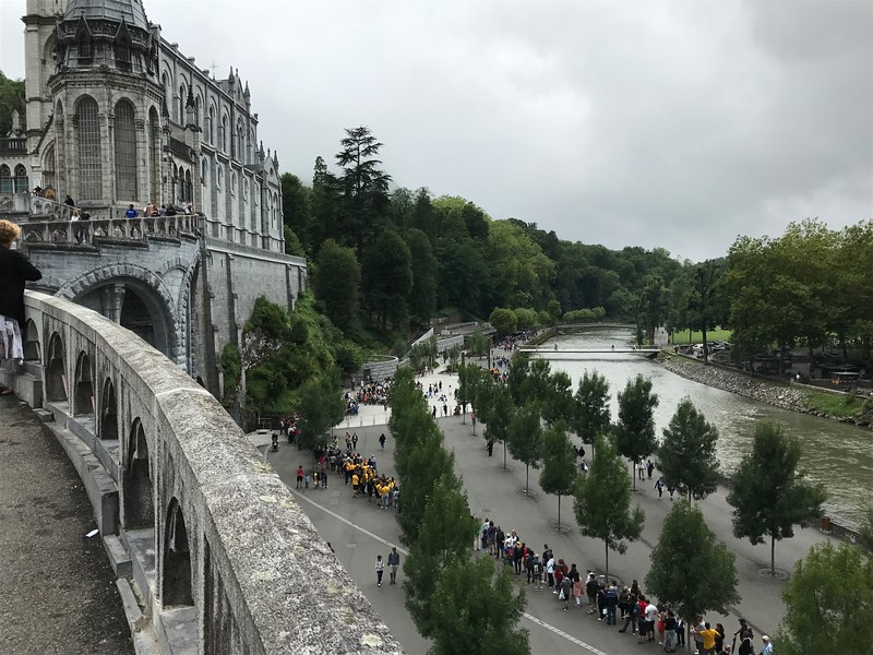 Line of people waiting to see the grotto. River Gave de Pau runs beside the grotto. The greenery below the cathedral wall shows how the basilica was built directly above the grotto where the people are either seated in front of or in line waiting to see it