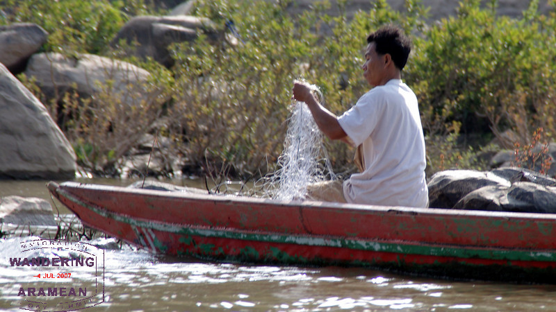 A fisherman on the Mekong River, untangling his nets