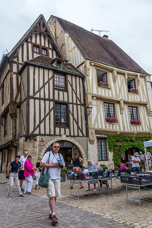 The writer, caught in a candid moment in Noyers-sur-Serein, in front of some 15th century houses, restored to perfection.